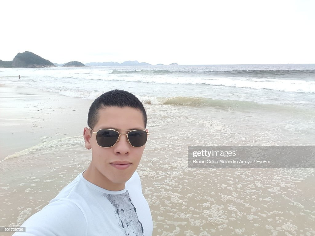 71abba22af6b Portrait Of Young Man Wearing Sunglasses Standing At Beach Against Clear  Sky : Stock Photo