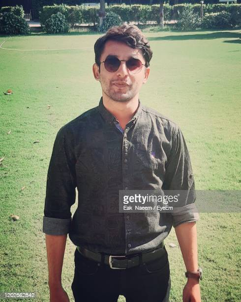 portrait of young man wearing sunglasses standing outdoors - pakistan stock pictures, royalty-free photos & images