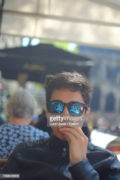 Portrait Of Young Man Wearing Sunglasses While Eating Food At Restaurant