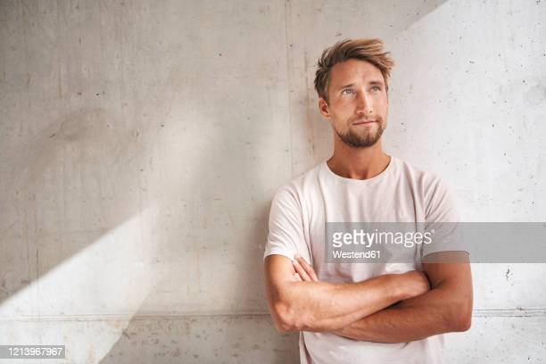 portrait of young man wearing t-shirt looking up - facial hair stock pictures, royalty-free photos & images
