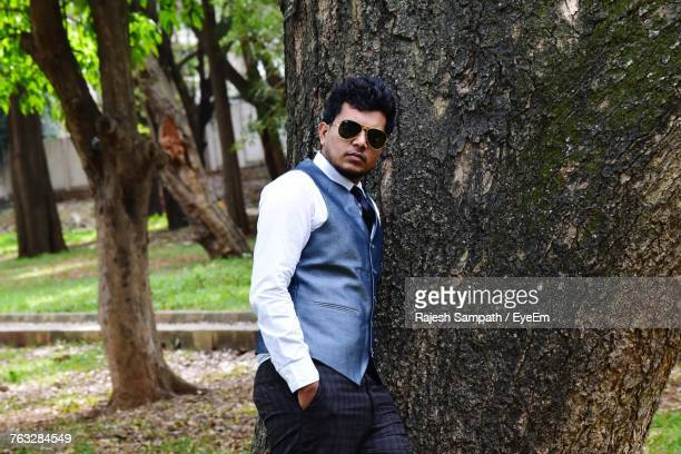 Portrait Of Young Man Wearing Waistcoat While Leaning On Tree At Park