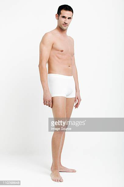 portrait of young man wearing white boxer shorts - shorts stock pictures, royalty-free photos & images