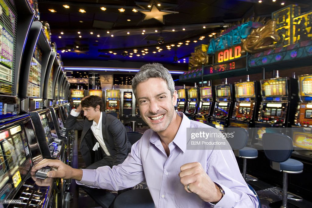 Portrait of young man winning at slot machines : Stock Photo