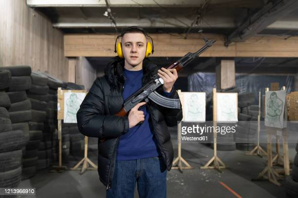 portrait of young man with a gun in shooting range - kalashnikov stock pictures, royalty-free photos & images