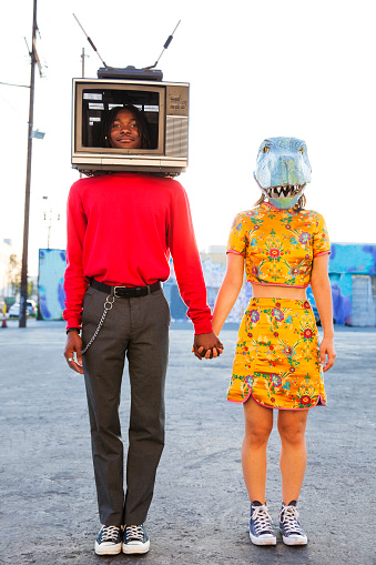 Portrait of young man with a television set on his head and a woman wearing a dinosaur mask - gettyimageskorea