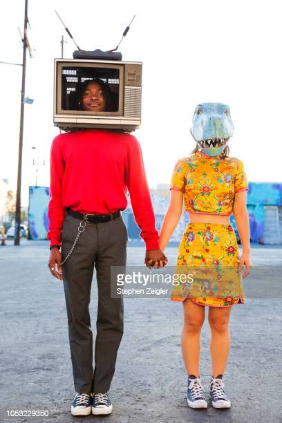 portrait of young man with a television set on his head and a woman wearing a dinosaur mask - gegensatz stock-fotos und bilder