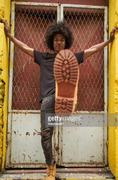 portrait of young man with afro kicking - kicking photos et images de collection