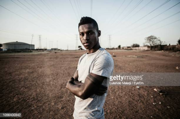 portrait of young man with arms crossed while standing on field - gauteng province stock pictures, royalty-free photos & images