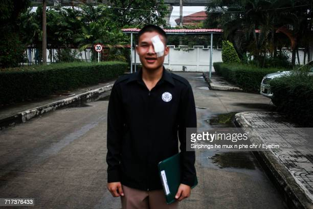 Portrait Of Young Man With Bandage On Eye Standing On Street