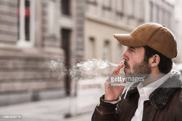 portrait of young man with baseball cap smoking cigarette - cigarette stock pictures, royalty-free photos & images