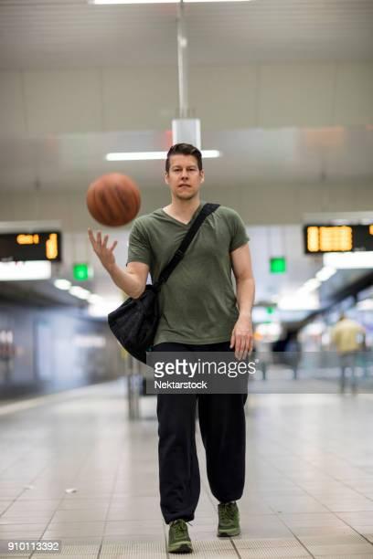 portrait of young man with basketball walking at railroad station platform - sac porté épaule photos et images de collection