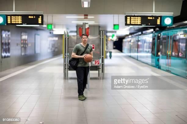 Portrait Of Young Man With Basketball Walking At Railroad Station Platform
