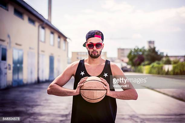 Portrait of young man with basketball wearing basecap and sunglasses