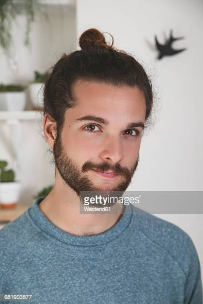 portrait of young man with beard and bun - man bun stock pictures, royalty-free photos & images