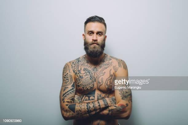portrait of  young man with beard, bare chest covered in tattoos, arms folded - korsade armar bildbanksfoton och bilder