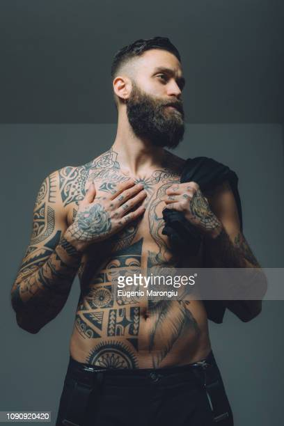 portrait of  young man with beard, bare chest covered in tattoos - chest barechested bare chested fotografías e imágenes de stock
