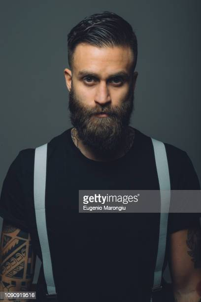 portrait of young man with beard, wearing trouser braces, tattoos on arms - suspenders stock pictures, royalty-free photos & images