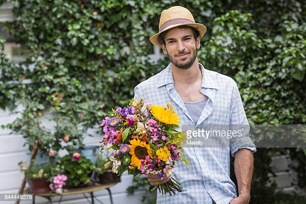 Portrait of young man with bunch of flowers in garden