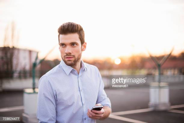 Portrait of young man with cell phone looking at distance