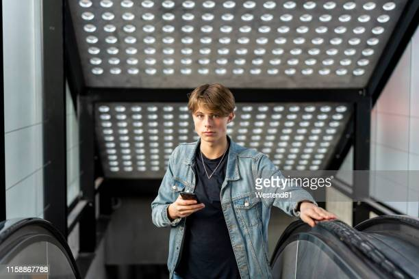 portrait of young man with cell phone on escalator - denmark stock pictures, royalty-free photos & images