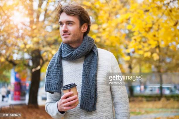 portrait of young man with coffee to go in autumn - só homens jovens imagens e fotografias de stock
