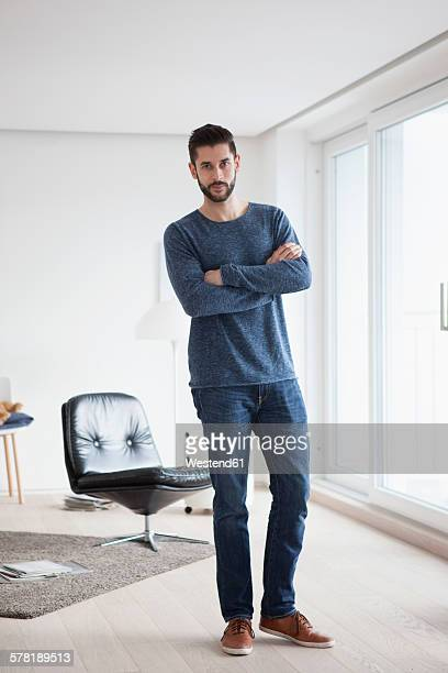 Portrait of young man with crossed arms standing in his living room