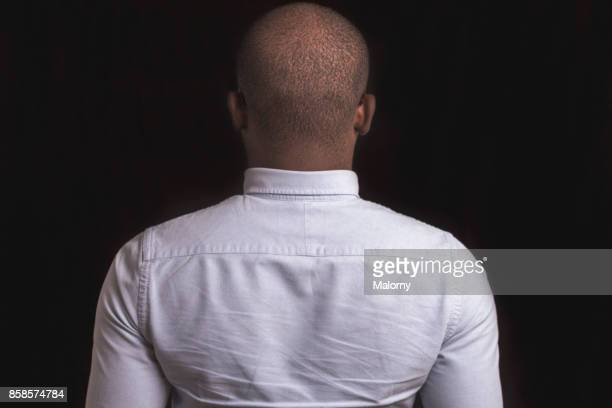 portrait of young man with dark skin standing in front of black background. - human back stock photos and pictures