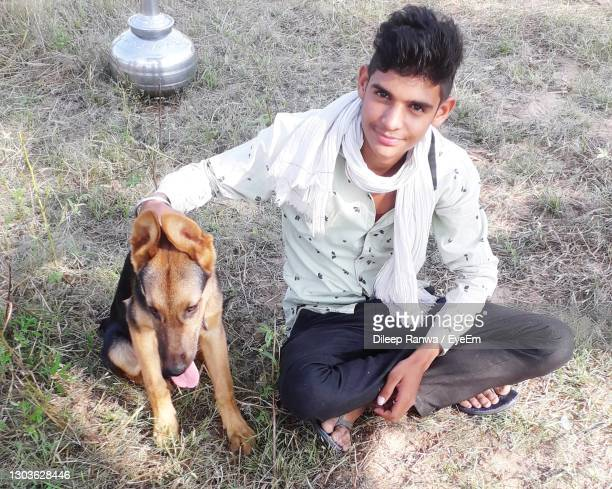 portrait of young man with dog on grass - chandigarh stock pictures, royalty-free photos & images