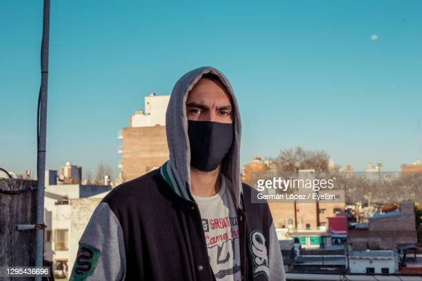 portrait of young man with face mask in city against clear sky - hooded top stock pictures, royalty-free photos & images