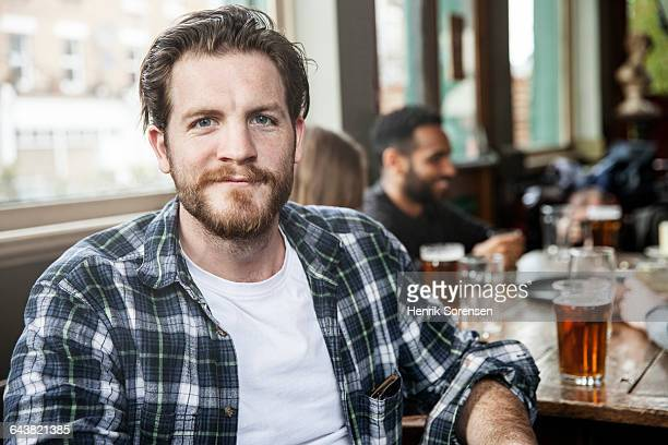 portrait of young man with friends at a pub - fully unbuttoned stock pictures, royalty-free photos & images