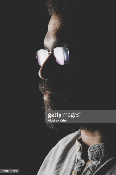 portrait of young man with glasses in dark background - jewish man stock photos and pictures