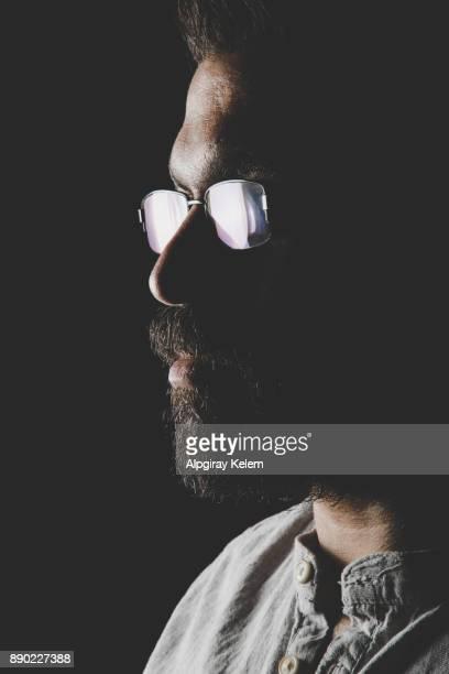 porträt des jungen mann mit brille in dunklem hintergrund - aktmodell mann stock-fotos und bilder