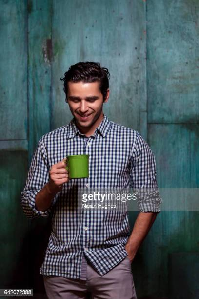 Portrait of young man with green coffee mug