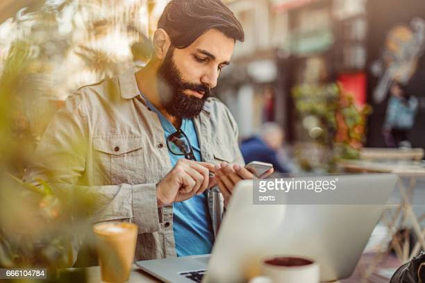 Portrait of young man with long beard working at cafe