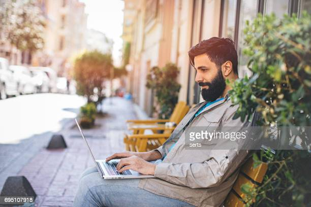 portrait of young man with long beard working at cafe - turkey middle east stock pictures, royalty-free photos & images