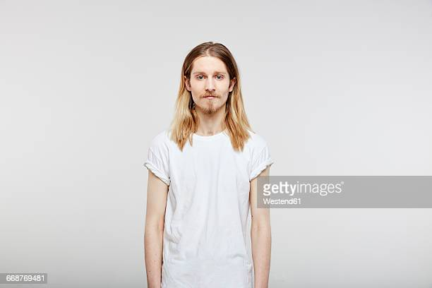 portrait of young man with long blond hair - lang haar stockfoto's en -beelden