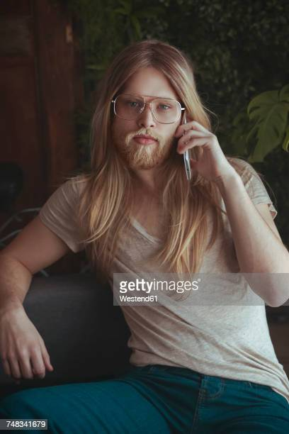 Portrait of young man with long hair and beard using smartphone at home
