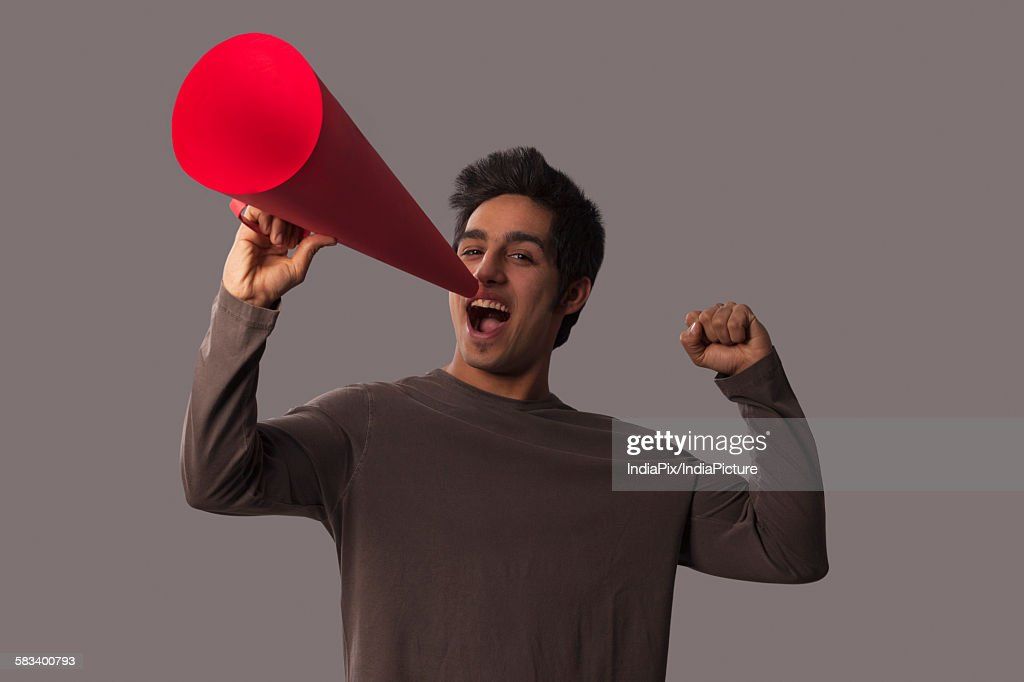 Portrait of young man with megaphone cheering : Stock Photo