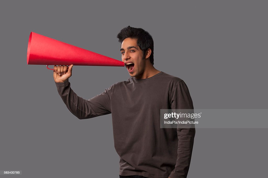 Portrait of young man with megaphone : Stock Photo