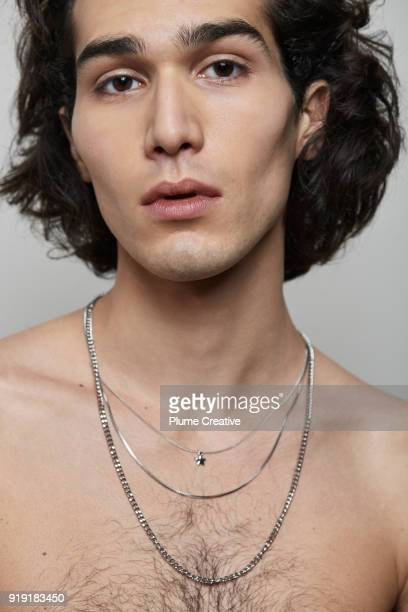 Portrait of young man with naked torso and necklaces