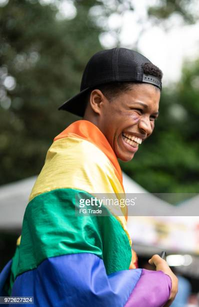 portrait of young man with rainbow flag - lgbtqi pride event stock pictures, royalty-free photos & images