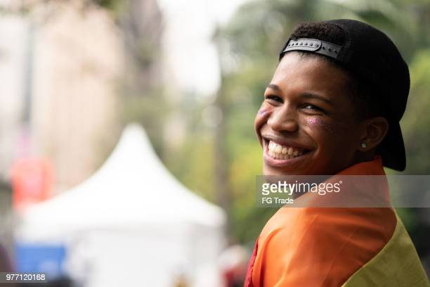 portrait of young man with rainbow flag - lgbtqi rights stock pictures, royalty-free photos & images