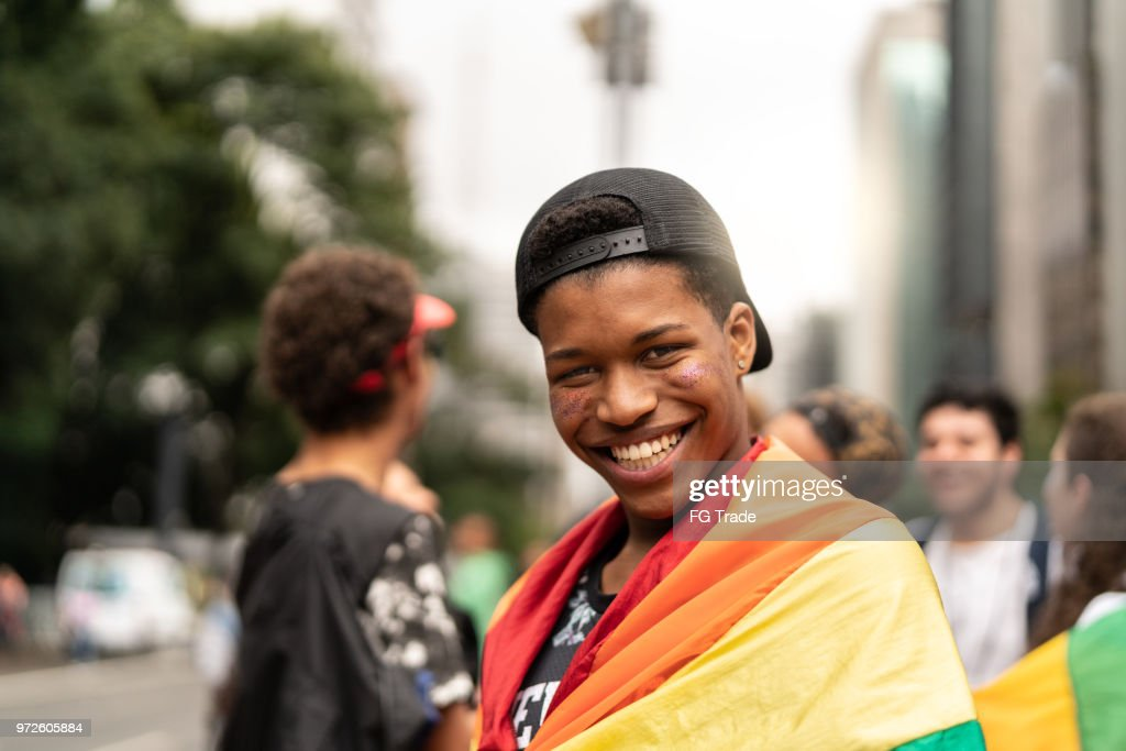 Portrait of young man with rainbow flag with friends on background at Gay Parade : Stock Photo