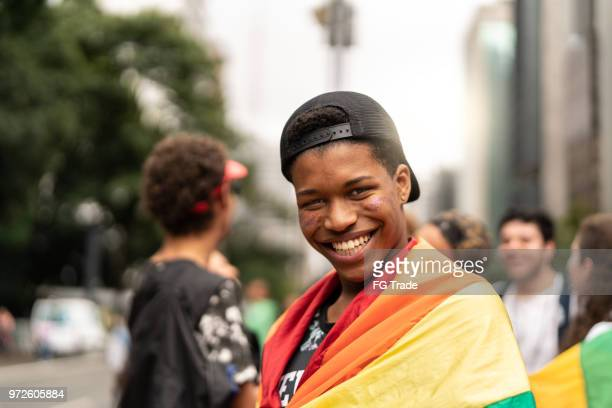 portrait of young man with rainbow flag with friends on background at gay parade - gay rights stock pictures, royalty-free photos & images