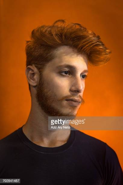 Portrait of young man with red hair against orange background