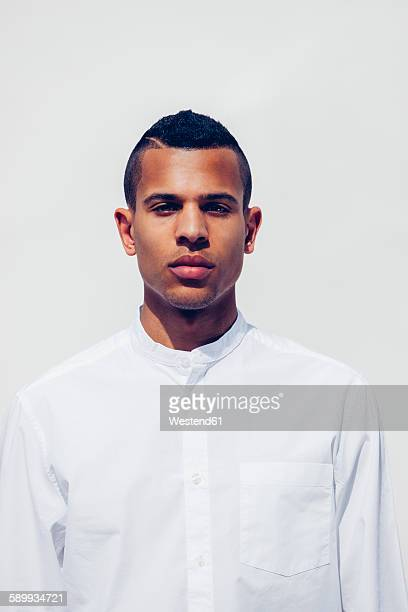 Portrait of young man with shaved hair wearing white shirt in front of white background