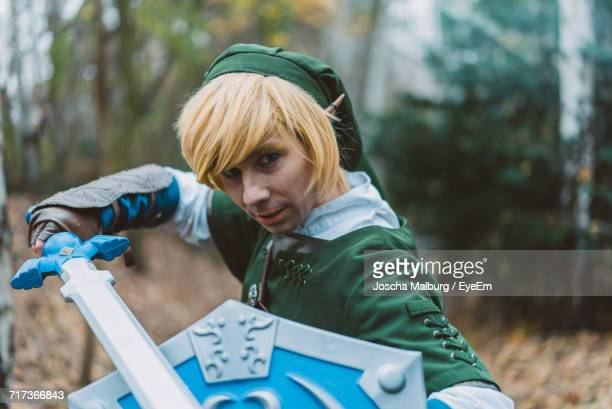 Portrait Of Young Man With Shield And Sword In Cosplay Costume
