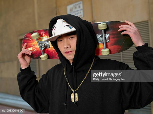 portrait of young man with skateboard, wearing hooded top - chav stock photos and pictures