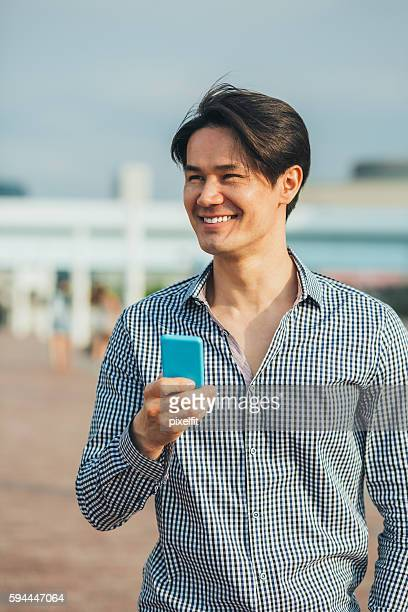 Portrait of young man with smart phone outdoors