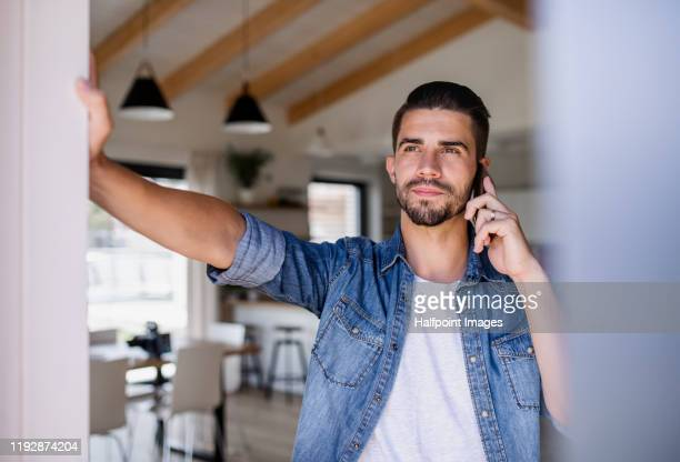 portrait of young man with smartphone standing indoors at home, making phone call. - デニムシャツ ストックフォトと画像